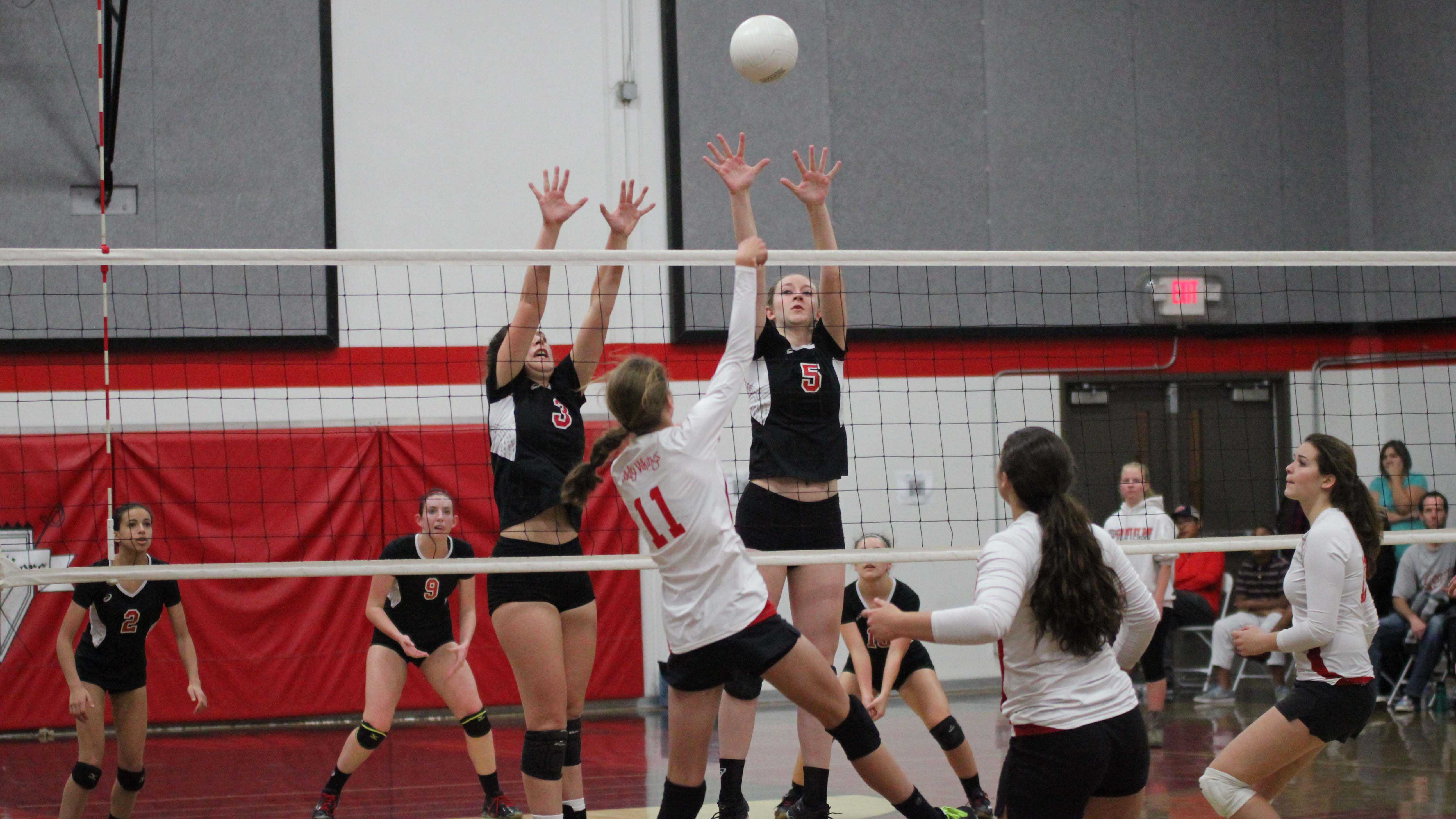 Junior Alexa Mathisen and senior Jenny Kerbs block a Victory Christian Viking's hit in the third set of the Cavs' first playoff game, Nov. 12.